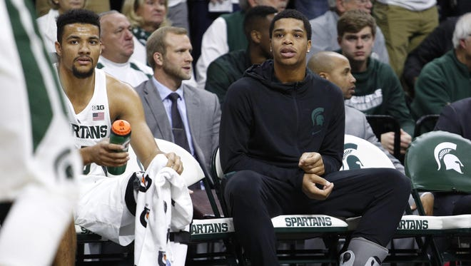 Michigan State freshman Miles Bridges (right) sits next to Kenny Goins on the Spartans' bench with a left ankle injury during a 80-76 win over Oral Roberts on Saturday.