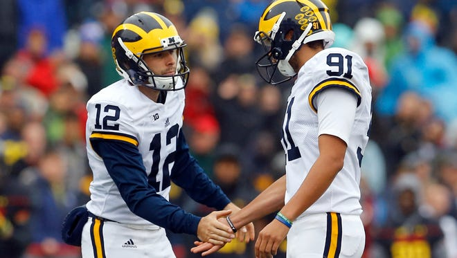 Michigan's Blake O'Neill, left, congratulates kicker Kenny Allen after Allen's successful field goal in the first half of an NCAA college football game against Maryland, Saturday, Oct. 3, 2015, in College Park, Md.