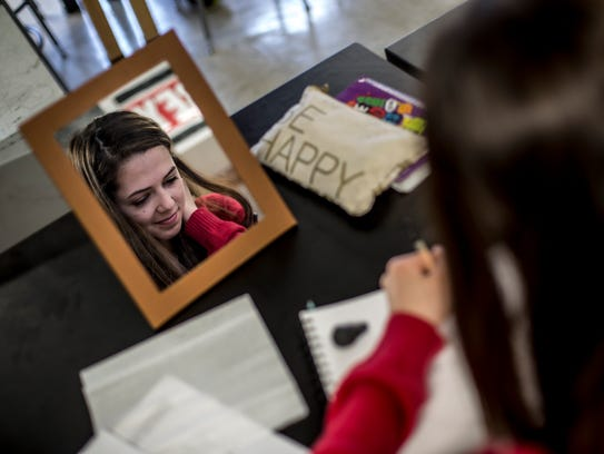 Christina Berels, 16, uses a mirror as she works on