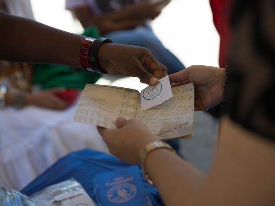Tamanda Chabvuta hands a passport sticker to Yamnei