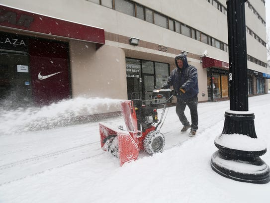 Lou Liguori of Highland uses a snowblower to clear