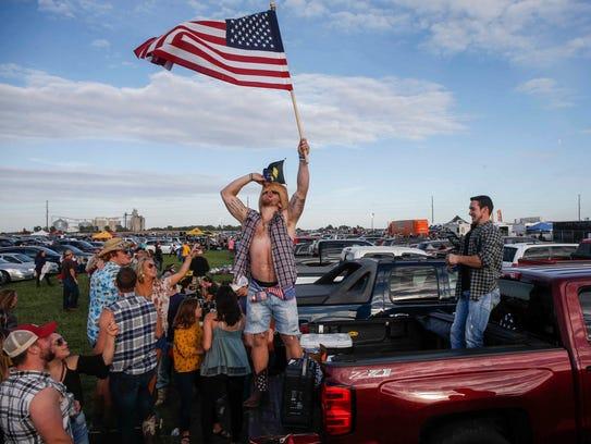 Ashton Clemons of Boone raises a U.S. flag from the