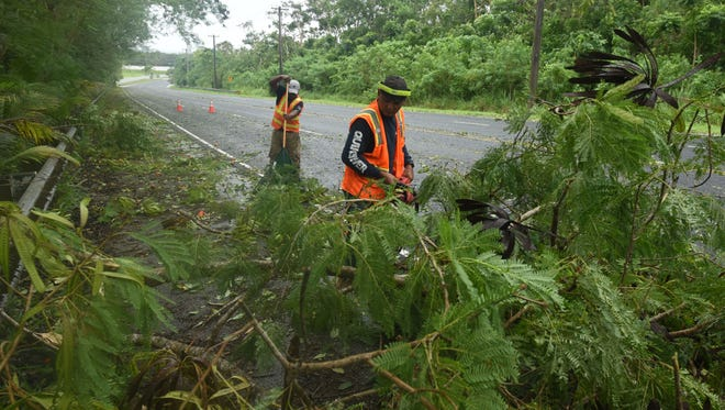 Piti Mayor Office employees, Paul G., front, and Ruben Renta, clean vegetation and other debris from Spruance Drive after the passage of Tropical Storm Maria on Thursday, July 5, 2018.