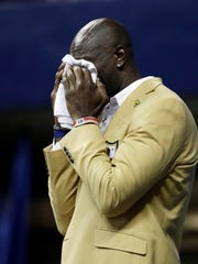 Former wide receiver Terrell Owens wipes tears as he delivers his Pro Football Hall of Fame speech on Saturday, Aug. 4, 2018, in Chattanooga, Tenn. Instead of speaking at the Hall of Fame festivities in Canton, Ohio, Owens celebrated his induction at the University of Tennessee at Chattanooga, where he played football and basketball and ran track. (AP Photo/Mark Humphrey)