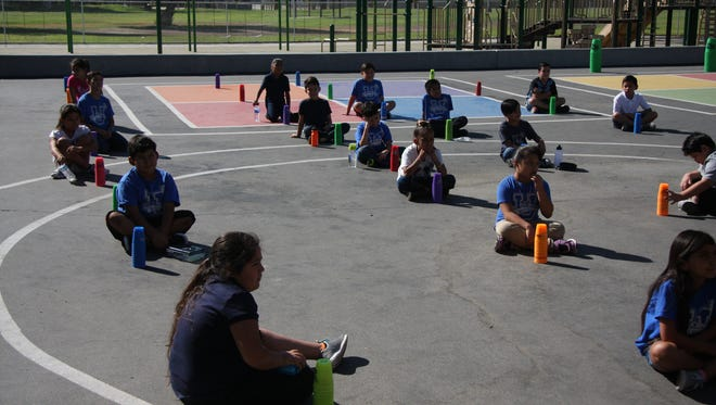 Students stack cups as a physical education activity.