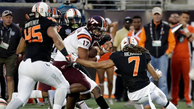 Virginia Tech quarterback and former Saline star Josh Jackson runs past Oklahoma State linebacker Chad Whitener (45) and safety Ramon Richards (7) for a 13-yard touchdown during the first half on Thursday.