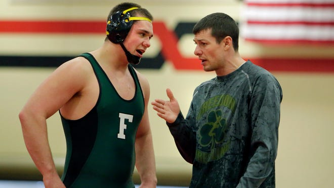 In this Post-Crescent Media file photo Freedom Coach Justin Lancaster talks to Reed Ambrosius. Lancaster has been named as coach of the year by the Wisconsin Wrestling Coaches Association.