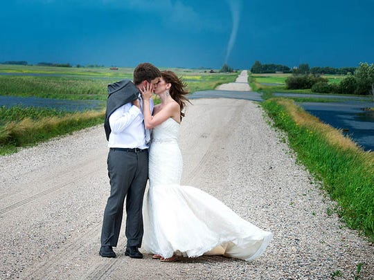 A wedding photographer in Canada caught a tornado in the background during an outdoor wedding photo shoot.