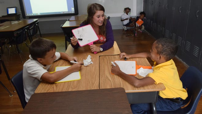 Jennifer Kirkikis (center) is a second-grade teacher at D.F. Huddle Elementary School in Alexandria. Here she helps two of her students Jaxon Thompson (left) and Kendall Williams with reading. Kirkikis is one of four Rapides Parish educators that The Town Talk is following this school year. They're all at different points in their careers with different experiences to share.