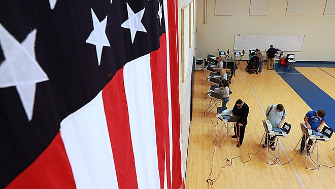 With a large American flag on the wall, people cast their ballot in the presidential election.