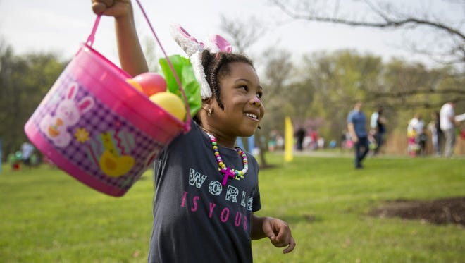 Julia Darko, 4, of Mason, shows off her overflowing bucket during a 2017 Easter egg hunt at Pioneer Park.