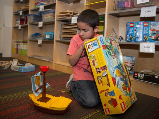 Six-year-old Emilio Cano plays with a Lego set at Centennial High School's Autism Resource Library.