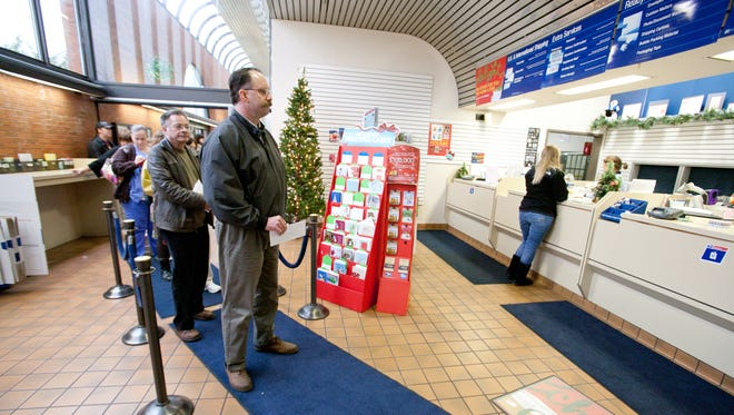 People stand in line to ship holiday packages in time for Christmas Day.