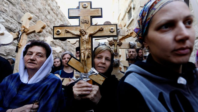 """Christian pilgrims carry wooden crosses along the path where Jesus walked, now known as the """"Via Dolorosa,"""" on Good Friday."""