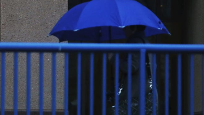 A woman tries to stay dry Thursday morning in Covington.