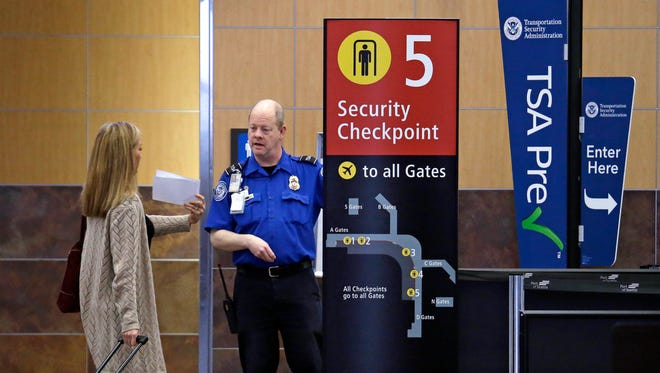 A passenger shows a boarding pass to a TSA agent at a security checkpoint at Seattle-Tacoma International Airport.