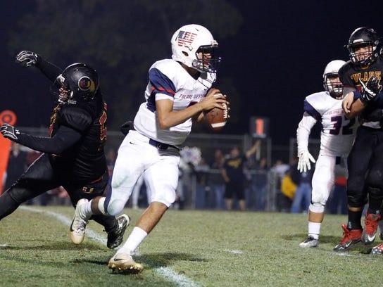 Tulare Western senior quarterback Andre Aguilar scrambles