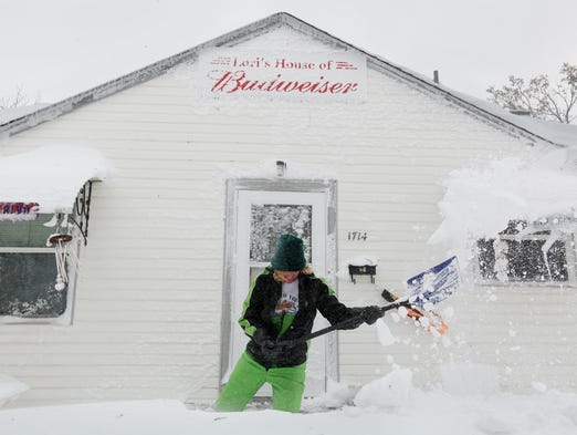 Lori Mehlberg shovels snow to clear a pathway to the front door of her home in Rapid City, S.D., on Oct. 5, 2013.  South Dakota emergency agencies are asking snowmobile operators in the area to help find motorists stranded by an autumn storm. The National Weather Service says the storm dumped at least 3.5 feet of wet, heavy snow in the Black Hills. Rapid City had 21 inches, but 31 inches was recorded just a mile southwest of the city.