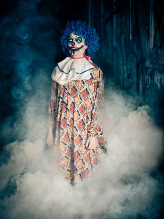 Crazy ugly grunge evil clown  making people shock and scared