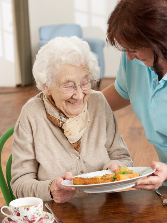 Senior Woman Being Served Meal By Carer