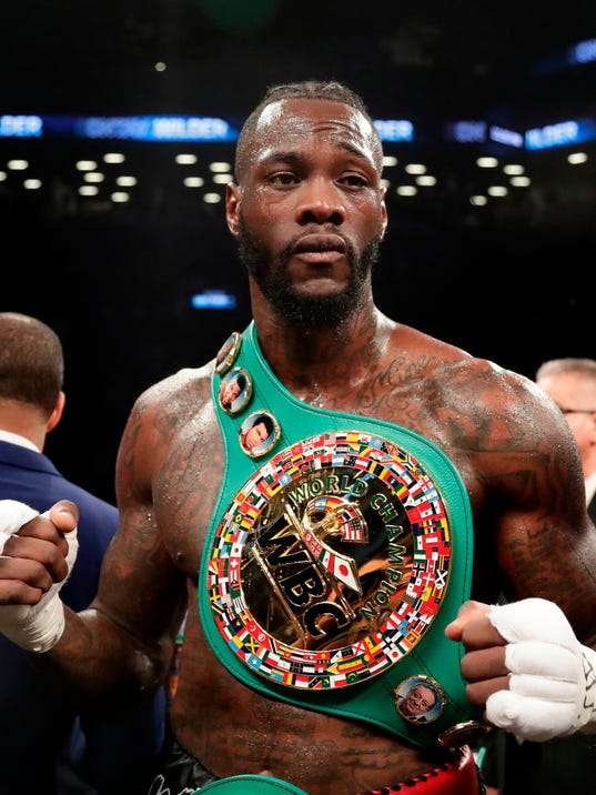 """FILE - In this March 3, 2018, file photo, Deontay Wilder poses for photographs after the WBC heavyweight champion defeated Luis Ortiz in New York. Wilder says he's ready to fight Anthony Joshua in a heavyweight unification bout, and is willing to travel overseas. Wilder cancelled a scheduled media conference call Tuesday, April 3, 2018, instead issuing a statement saying he's """"ready to come to the (United Kingdom) for my next fight."""" (AP Photo/Frank Franklin II, File)"""