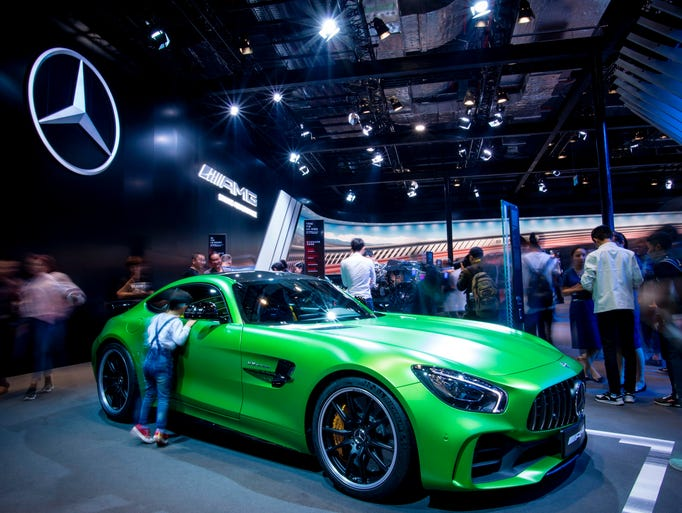 Visitors look at cars from Mercedes during the public