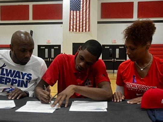 With the support of Derrick Long Sr. (left) and Latora Gooden (right), Corry Long of Hughes High School signs his his letter of intent to play basketball for Stony Brook University, November 9.