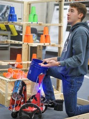 Senior David Velez prepares a test run of the Scorcher, a robot that knocks down plastic cups representing fire, clears chemical drums, and retrieves bodies from the the emergency zone.