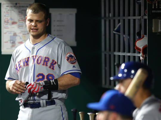 New York Mets catcher Devin Mesoraco (29) returns to the dugout after a pinch-hit at bat in the ninth inning during a National League baseball game between the New York Mets and the Cincinnati Reds, Tuesday, May 8, 2018, at Great American Ball Park in Cincinnati. Cincinnati won 7-2.