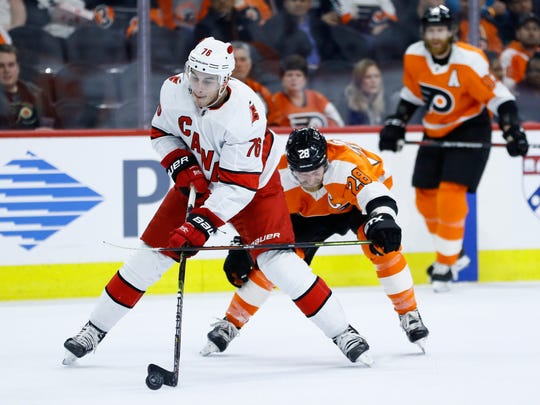 Carolina Hurricanes' Brady Skjei (76) tries to keep away from Philadelphia Flyers' Claude Giroux (28) during the second period of an NHL hockey game, Thursday, March 5, 2020, in Philadelphia. (AP Photo/Matt Slocum)