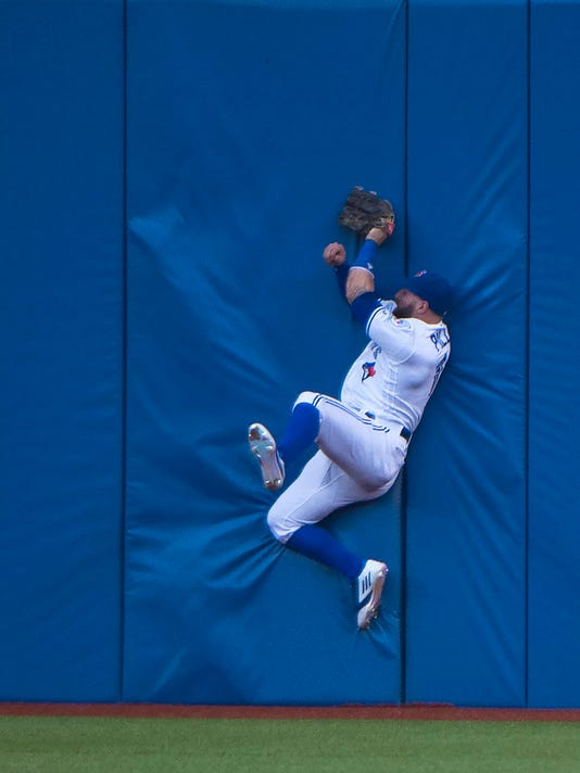 RETRANSMISSION TO CLARIFY THAT THE BATTER WAS OUT - Toronto Blue Jays center fielder Kevin Pillar makes a diving catch against the wall on a line drive by Arizona Diamondbacks left fielder Peter O'Brien during the fourth inning of a baseball game, Tuesday, June 21, 2016, in Toronto. (Nathan Denette/The Canadian Press via AP) MANDATORY CREDIT