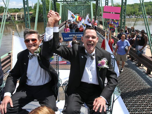 Charles Young, left, and Fred Blank of Tinicum, Pa., celebrate their marriage by riding on a float over the bridge between Lambertville and New Hope. The Bridge to Equality event takes place in support of marriage equality in Pa. The parade started near Lambertville City Hall, stopped on Bridge Street for the marriage ceremony, and then continued over the bridge into New Hope, Pa., May 17, 2014. Lambertville NJ. Staff  Kathy Johnson BRI 0518 Bridge to Equality