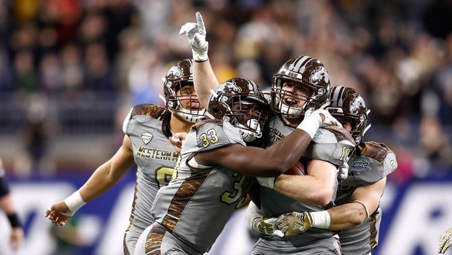 Robert Spillane (center right) of the Western Michigan Broncos celebrates his fourth quarter interception with Asantay Brown (left), Eric Assoua (center left), and Justin Tranquill (right) while playing the Ohio Bobcats.