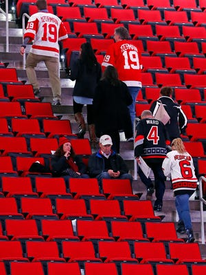 Detroit Red Wings and Carolina Hurricane fans leave their seats following the cancellation of the Red Wings game with the Carolina Hurricanes due to a problem with the ice in the PNC Arena