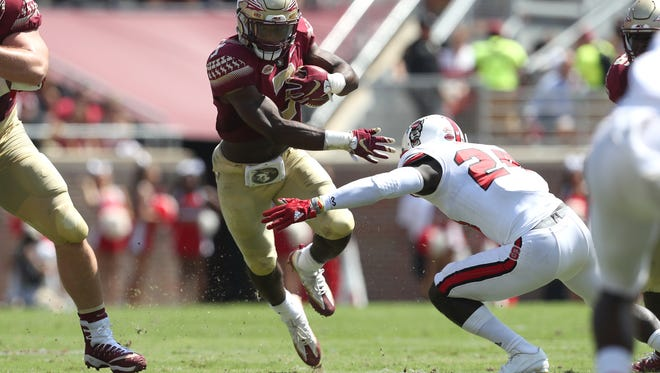 FSU's Cam Akers streaks past NC State's Shawn Boone during the Seminoles home opener at Doak Campbell Stadium on Saturday.