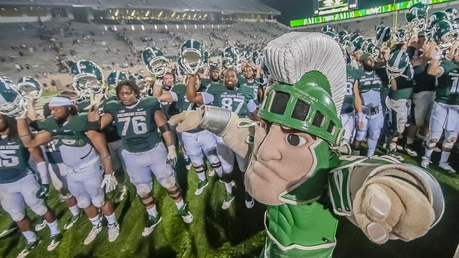 Sparty and members of the MSU football team sing the MSU fight song after their win over Western Michigan on Aug. 30, 2013.