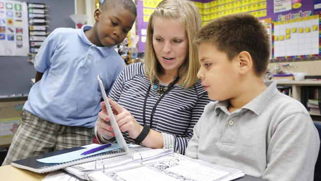 Second grade teacher Natasha Carr helps Manuel Barradas Gaeta with a spelling ABC order exercise as Kenye Allen, left, looks on Thursday, September 10, 2015, at Miller Elementary School. Carr is in her first year of teaching after graduating from Purdue University.