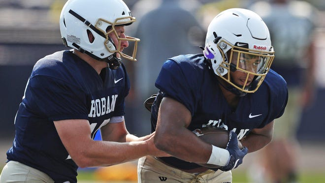Hoban quarterback Shane Hamm hands the ball off to running back Victor Dawson during practice Wednesday.