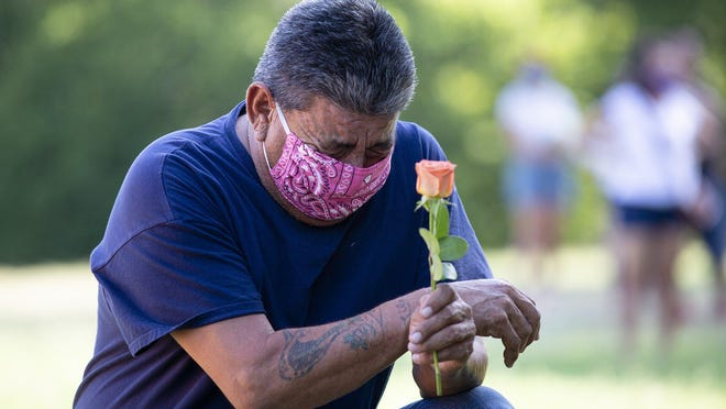 """Eddie Garcia, 61, gets emotional Sunday while saying a prayer for Vanessa Guillen, a Fort Hood soldier whose remains were recently found. """"It hurts a lot even though I don't know her,"""" Garcia said. Hundreds of people walked from Metz Neighborhood Park to Edward Rendon Park where a candlelight vigil was held to honor Guillen."""