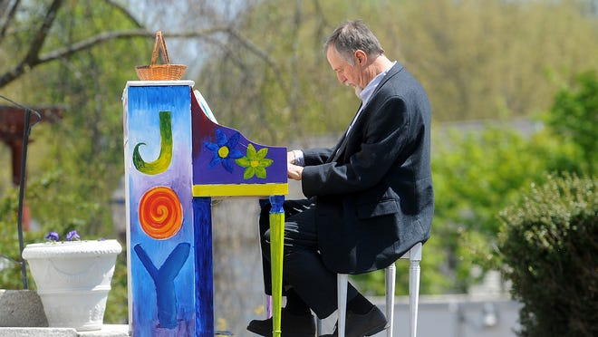 Jack Hunter, Hudson's director of planning and community development, plays the outdoor Community Piano Project piano in front of the Unitarian Church. Hunter announced he will retire on Aug. 1.