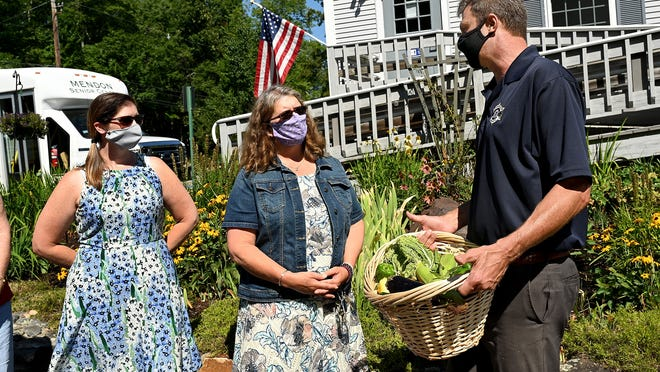 Amy Wilson Kent, center, Mendon Senior Services director, accepts a produce delivery Tuesday from Worcester County Sheriff Lewis Evangelidis, right, in front of the Mendon Senior Center. The vegetables are grown on the grounds of the Worcester County Jail and House of Correction in West Boylston.