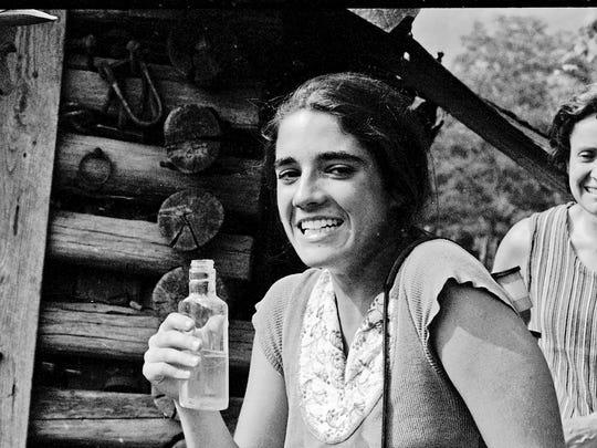 Allyson Riclitis tries moonshine as Marie Cirillo looks on while visiting Jim Huddleston's home near Eagan, Tenn, in 1973.
