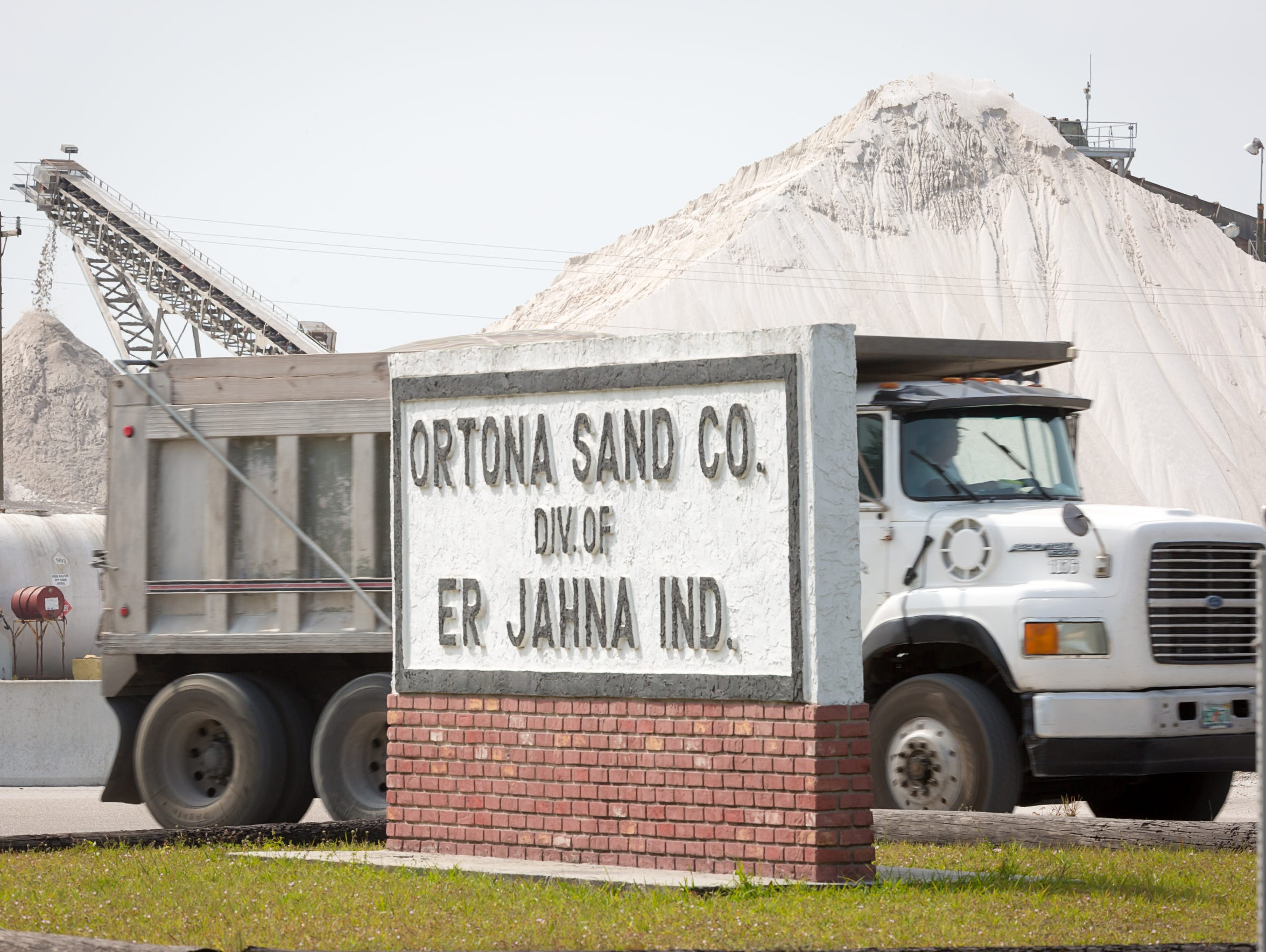 Dump trucks carry sand from an inland deposit at the