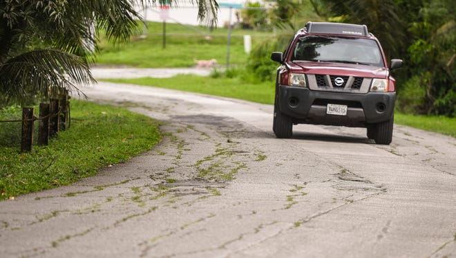 in this Feb. 9 file photo, a motorist resorts to travelling in the center of Erskin Drive in Agat to avoid uneven and cracking sections of pavement that riddle the roadway.