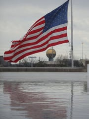 An American flag flies over the Food City off Western Avenue and reflects off the wet roof, as the Sunsphere stands in the background on Wednesday, Feb. 24, 2016. (CAITIE MCMEKIN/NEWS SENTINEL)