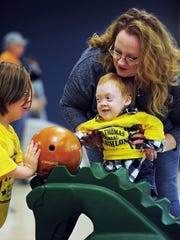 Emma Thomas, 14 (left), helps Brenden Baker and his mother, Kim, roll their bowling ball Feb. 8, 2014, at the seventh annual Joseph Thomas Memorial Triathlon at PrimeTime Entertainment Center.