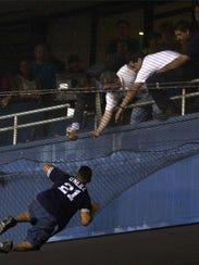 Yankees security guards reach for a fan who fell onto
