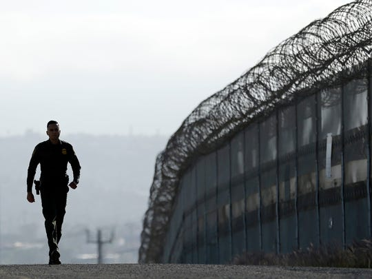 n this June 22, 2016, photo, Border Patrol agent Eduardo Olmos walks near the secondary fence separating Tijuana, Mexico, background, and San Diego in San Diego.