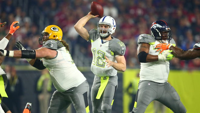 Team Carter offensive guard and Catholic graduate Josh Sitton of the Green Bay Packers, left, blocks for quarterback Andrew Luck of the Indianapolis Colts (12) as he throws a pass against Team Irvin in the 2015 Pro Bowl at University of Phoenix Stadium.