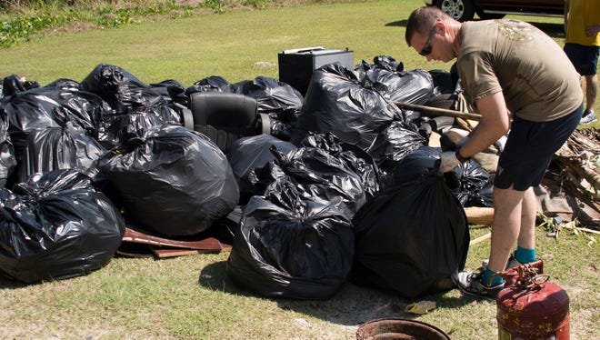Electronics Technician Nuclear 1st Class Bryan Schmidt, assigned to Performance Monitoring Team detachment Guam adds his trash bag to other bags behind the cemetery in Agat April 20.